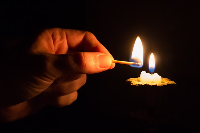 Lighting a candle in memory of a loved one.